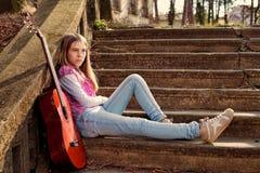 Chica joven con la expresión triste en su cara contra las escaleras de piedra viejas Imagen de archivo