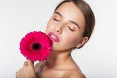 Chica joven con la flor sin defectos de la piel y del rojo Imagenes de archivo