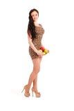 Chica joven con la fruta recolectada en su vestido Imagen de archivo libre de regalías