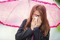 Chica joven con la gripe que sopla su nariz con un papel seda debajo de la lluvia de primavera Fotografía de archivo libre de regalías