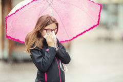 Chica joven con la gripe que sopla su nariz con un papel seda debajo de la lluvia de primavera Fotos de archivo