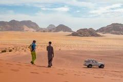 Chica joven con la guía local beduina en un viaje del jeep en un desierto rojo extenso de la arena de Wadi Rum, Medio Oriente, Jo imagen de archivo
