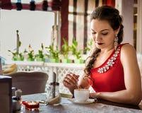Chica joven con la guadaña en un café Foto de archivo