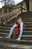 Chica joven con la guitarra que se sienta en las escaleras de piedra y que mira lejos Imagen de archivo