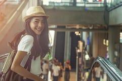 Chica joven con la maleta abajo de la escalera móvil Fotos de archivo libres de regalías