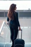 Chica joven con la maleta abajo de la escalera móvil Imagenes de archivo