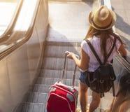 Chica joven con la maleta abajo de la escalera móvil traveling Fotografía de archivo