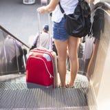 Chica joven con la maleta roja que se coloca en la escalera móvil Imagen de archivo libre de regalías
