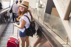 Chica joven con la maleta roja que se coloca en la escalera móvil concepto del recorrido Fotos de archivo libres de regalías