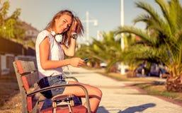 Chica joven con la mirada del monopatín y de los auriculares Imagen de archivo