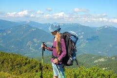 Chica joven con la mochila en montañas Foto de archivo libre de regalías