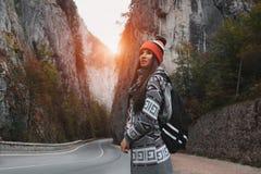 Chica joven con la mochila en montañas cerca del camino Fotos de archivo libres de regalías