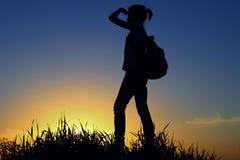 Chica joven con la mochila que disfruta de puesta del sol Viajero turístico en la puesta del sol Imagen de archivo libre de regalías