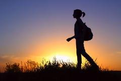 Chica joven con la mochila que disfruta de puesta del sol Viajero turístico en la puesta del sol Imagen de archivo
