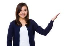 Chica joven con la palma abierta de la mano para mostrar algo Foto de archivo