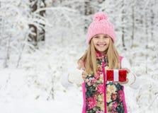 Chica joven con la pequeña caja de regalo roja que muestra los pulgares para arriba en bosque del invierno Imagen de archivo libre de regalías