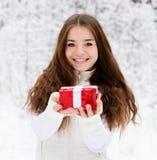 Chica joven con la pequeña caja de regalo roja que se coloca en bosque del invierno Foto de archivo