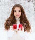 Chica joven con la pequeña caja de regalo roja que se coloca en bosque del invierno Fotografía de archivo libre de regalías