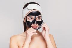 Chica joven con la purificación de la mascarilla negra imagenes de archivo