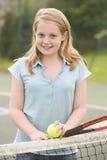 Chica joven con la raqueta en la sonrisa del campo de tenis Imagen de archivo libre de regalías