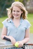 Chica joven con la raqueta en la sonrisa del campo de tenis Imagen de archivo