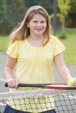 Chica joven con la raqueta en la sonrisa del campo de tenis Foto de archivo libre de regalías