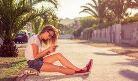 Chica joven con la sentada del monopatín y del smartphone Imagen de archivo libre de regalías