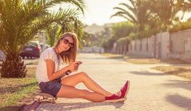 Chica joven con la sentada del monopatín y del smartphone Fotos de archivo libres de regalías