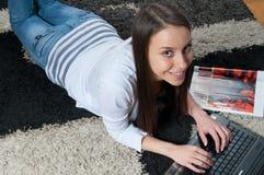 Chica joven con la sonrisa de la computadora portátil Imagen de archivo libre de regalías