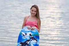 Chica joven con la sonrisa de la tabla hawaiana Imágenes de archivo libres de regalías