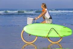 Chica joven con la tabla hawaiana y la bicicleta Foto de archivo libre de regalías