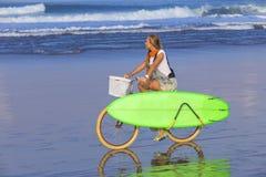 Chica joven con la tabla hawaiana y la bicicleta Imagen de archivo