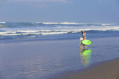 Chica joven con la tabla hawaiana y la bicicleta Imagen de archivo libre de regalías