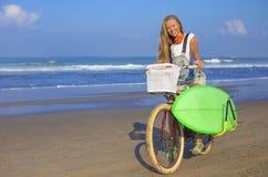 Chica joven con la tabla hawaiana y la bicicleta Imágenes de archivo libres de regalías