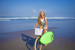 Chica joven con la tabla hawaiana y la bicicleta Fotografía de archivo libre de regalías