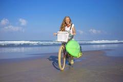 Chica joven con la tabla hawaiana y la bicicleta Fotos de archivo libres de regalías