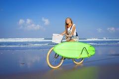Chica joven con la tabla hawaiana y la bicicleta Imagenes de archivo