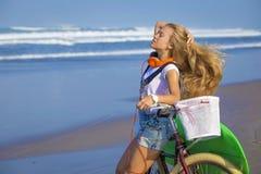 Chica joven con la tabla hawaiana y la bicicleta Fotos de archivo