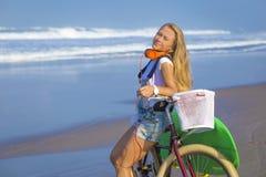 Chica joven con la tabla hawaiana y la bicicleta Foto de archivo