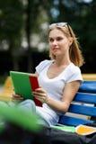 Chica joven con la tableta que se sienta en banco de parque en medio de la naturaleza Fotografía de archivo libre de regalías