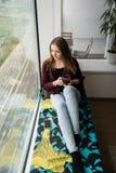 Chica joven con la taza de té en la ventana Foto de archivo libre de regalías
