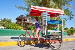 Chica joven con la tienda del Caribe del triciclo Fotografía de archivo libre de regalías