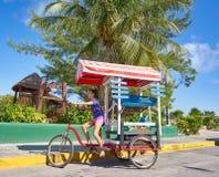 Chica joven con la tienda del Caribe del triciclo Fotos de archivo