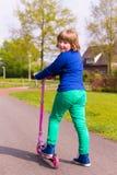 Chica joven con la vespa rosada del empuje que mira detrás Foto de archivo
