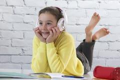 Chica joven con las auriculares que hacen la preparación en piso Fotografía de archivo