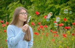 Chica joven con las burbujas de jabón en bosque Foto de archivo
