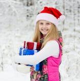 Chica joven con las cajas de regalo de la pila en bosque del invierno Fotos de archivo