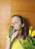 Chica joven con las flores amarillas y el pájaro verde (pequeño loro) Foto de archivo libre de regalías