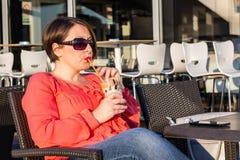 Chica joven con las gafas de sol que bebe el café y que goza de Sunny Day Outside hermoso foto de archivo