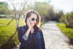 Chica joven con las gafas de sol que habla en un teléfono celular Imagen de archivo libre de regalías